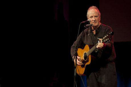 Cormac McCarthy playing guitar onstage